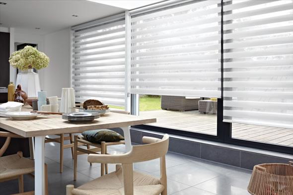 A Cortina Rolô Double Vision é moderna e prática, permite privacidade sem prejudicar a vista para a paisagem externa, diferenciando a decoração do ambiente, com tecidos paralelos que se alinham e desalinham para ajustar a visibilidade externa.